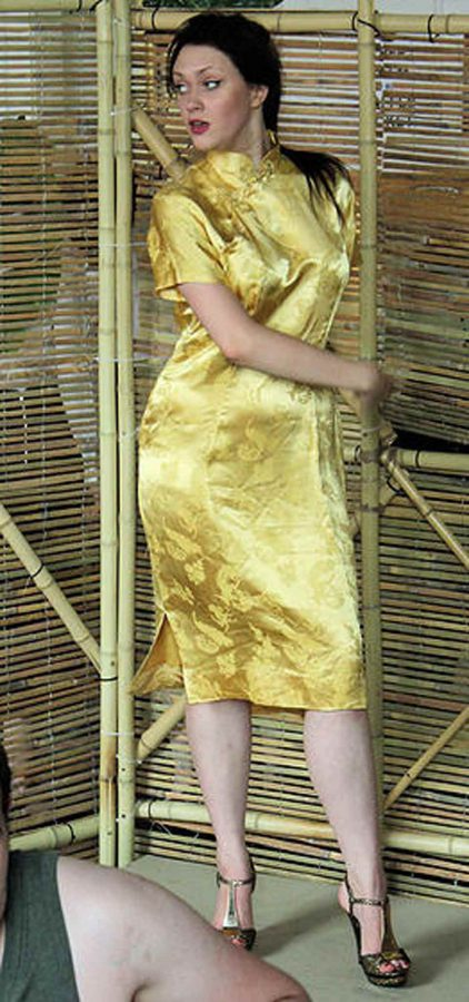 Kim in golden Vietnamese Ao Dai dress in scene from Miss Saigon
